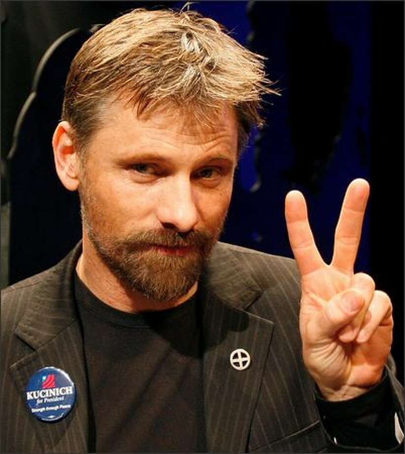 "Actor Viggo Mortensen makes a peace sign before the start of a panel discussion about an upcoming mini-series entitled ""The People Speak"", Jan. 9, 2008, at Emerson College in Boston. Production of the series, which is an adaptation of the book by Howard Zinn, began in Boston on Jan. 8 and will continue throughout the Spring. (AP Photo/Michael Dwyer)"