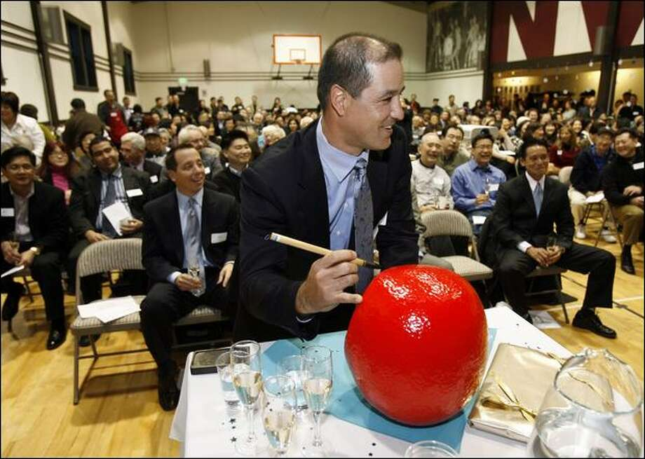 Mariners manager Don Wakamatsu paints an eye on a traditional Daruma doll during a welcoming reception hosted by Seattle's Asian Pacific Islander community. Photo: Mike Urban/Seattle Post-Intelligencer