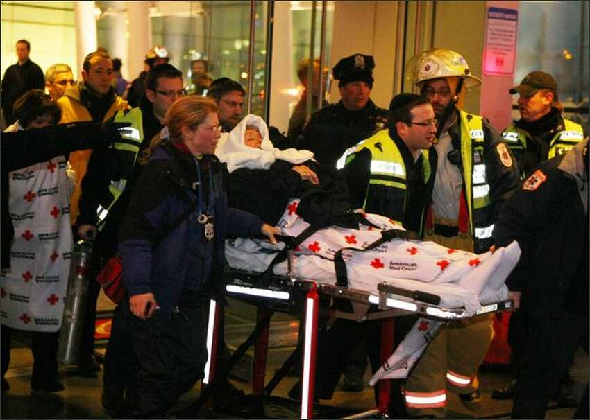 A passenger of US Airways flight 1549 is carried out on a stretcher from a Hudson River terminal in New York City.