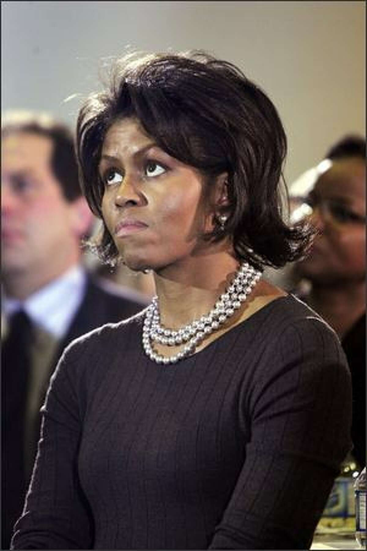 Michelle Obama, wife of Senator Barack Obama (D-IL), listen to her husband address a crowd gathered for a campaign rally at Central Middle School Feb. 10, 2007, in Waterloo, Iowa. U.S. Sen. Barack Obama (D-IL) announced at a rally in Sprinfield, Illinois Feb. 10 that he would seek the Democratic nomination for U.S. President.