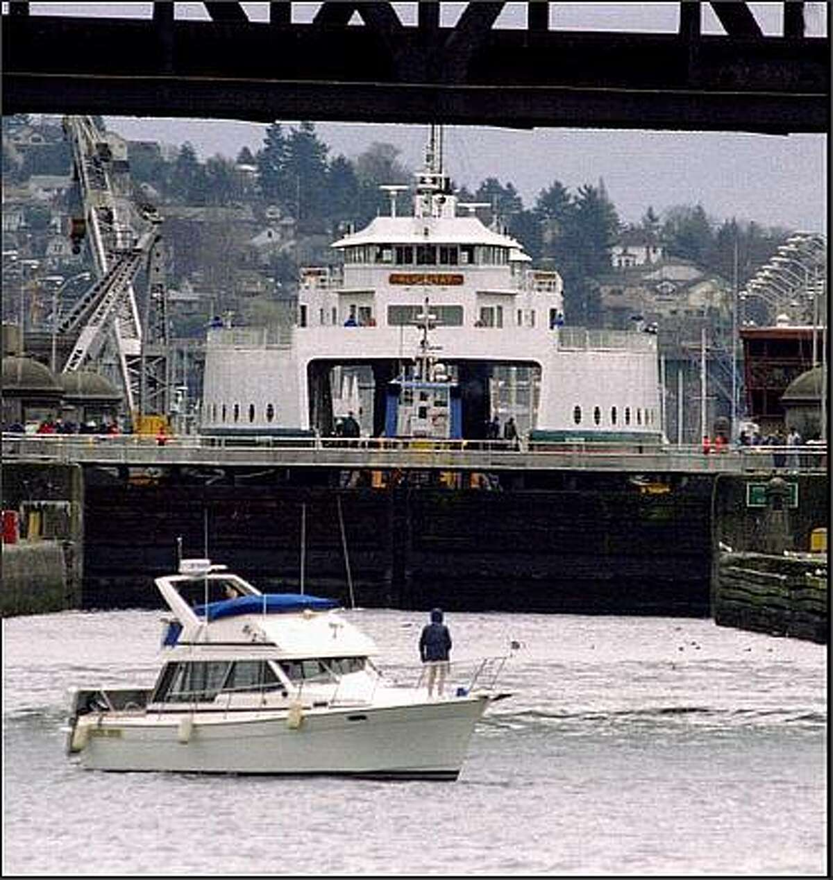 A cruiser waits its turn in the Ballard Locks as the Washington State Ferry Klickitat begins its descent to sea level after undergoing minor repairs in a Lake Union drydock. The ferry was is returning to service on the Port Townsend-Keystone route. The lock is 80 feet across, a tight squeeze. March 5, 1995.