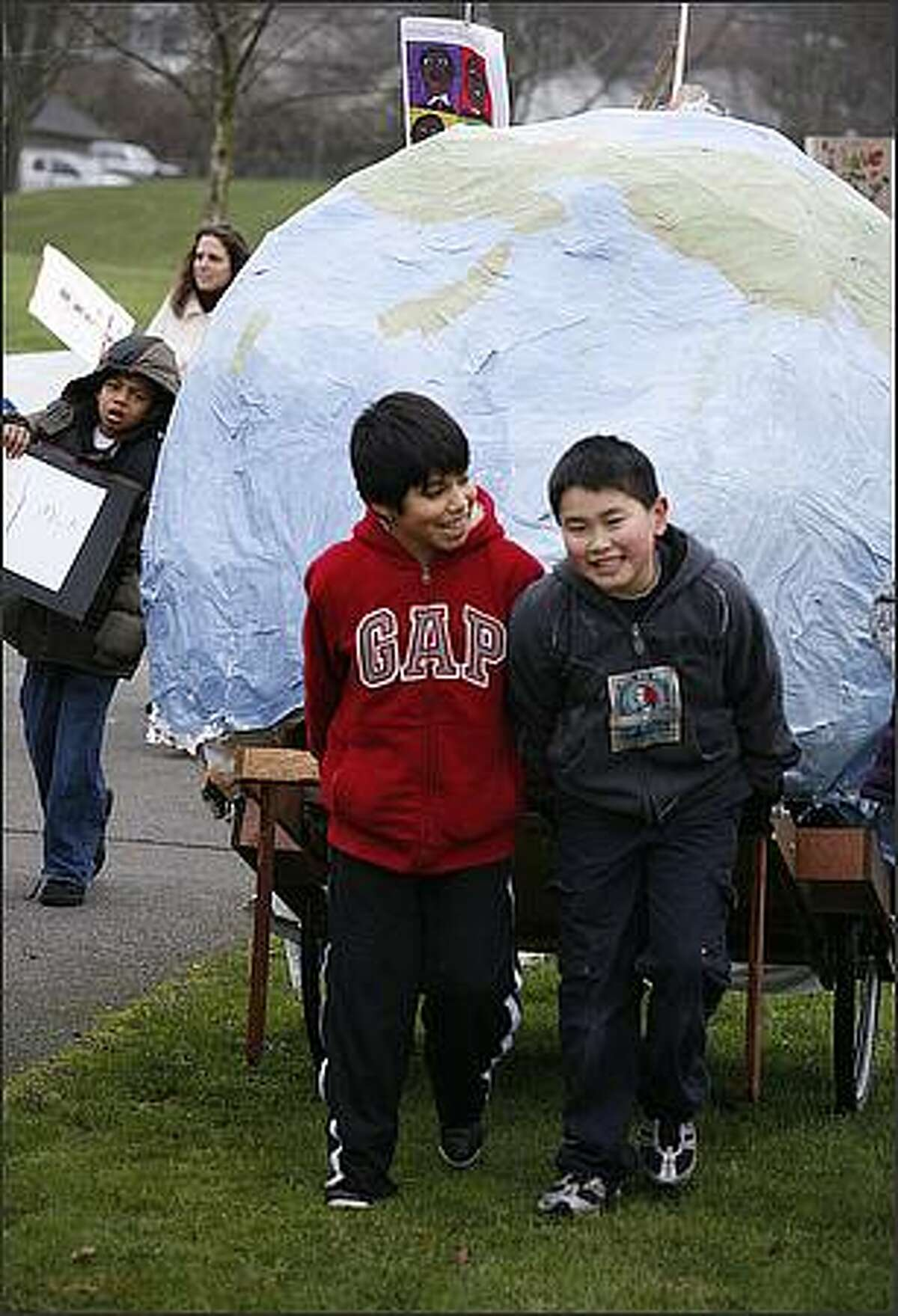 Giddens School classmates Matias Lazlo-Fanning, 10, and his buddy Alex Ono, 10, pulled a cart carrying a huge paper mache globe.