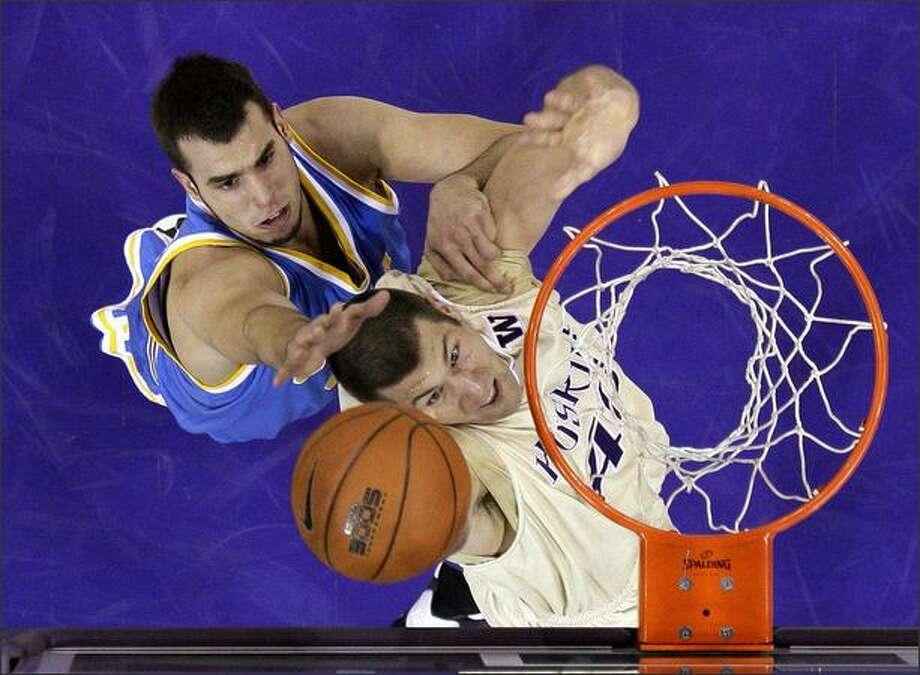Washington's Jon Brockman, right, gets a shot past UCLA's Nikola Dragovic in the first half. (AP Photo/Elaine Thompson) Photo: / Associated Press