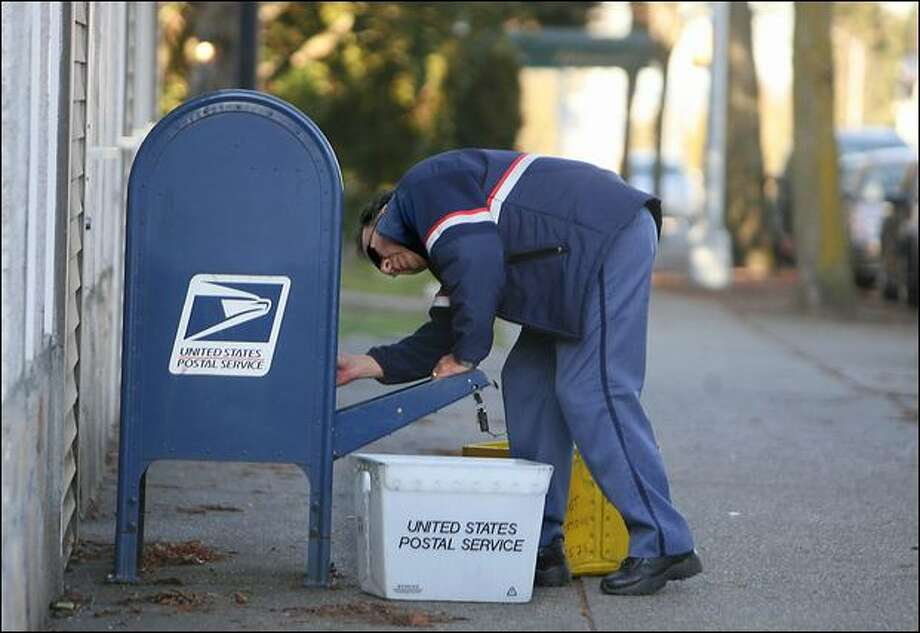 Jorge Santis picks up the mail Monday at the collection box on the corner of California Avenue Southwest and Southwest College Street. Photo: Scott Eklund/Seattle Post-Intelligencer