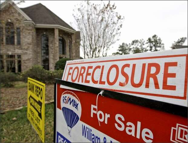 Bank repossession, foreclosure and for sale signs sit outside a foreclosed home in Houston. Two retired FBI officials asserted that the Bush administration was thoroughly briefed on the mortgage fraud crisis and its potential to cascade out of control, but made the decision not to give back to the FBI the agents it needed to address the problem. Photo: / Associated Press