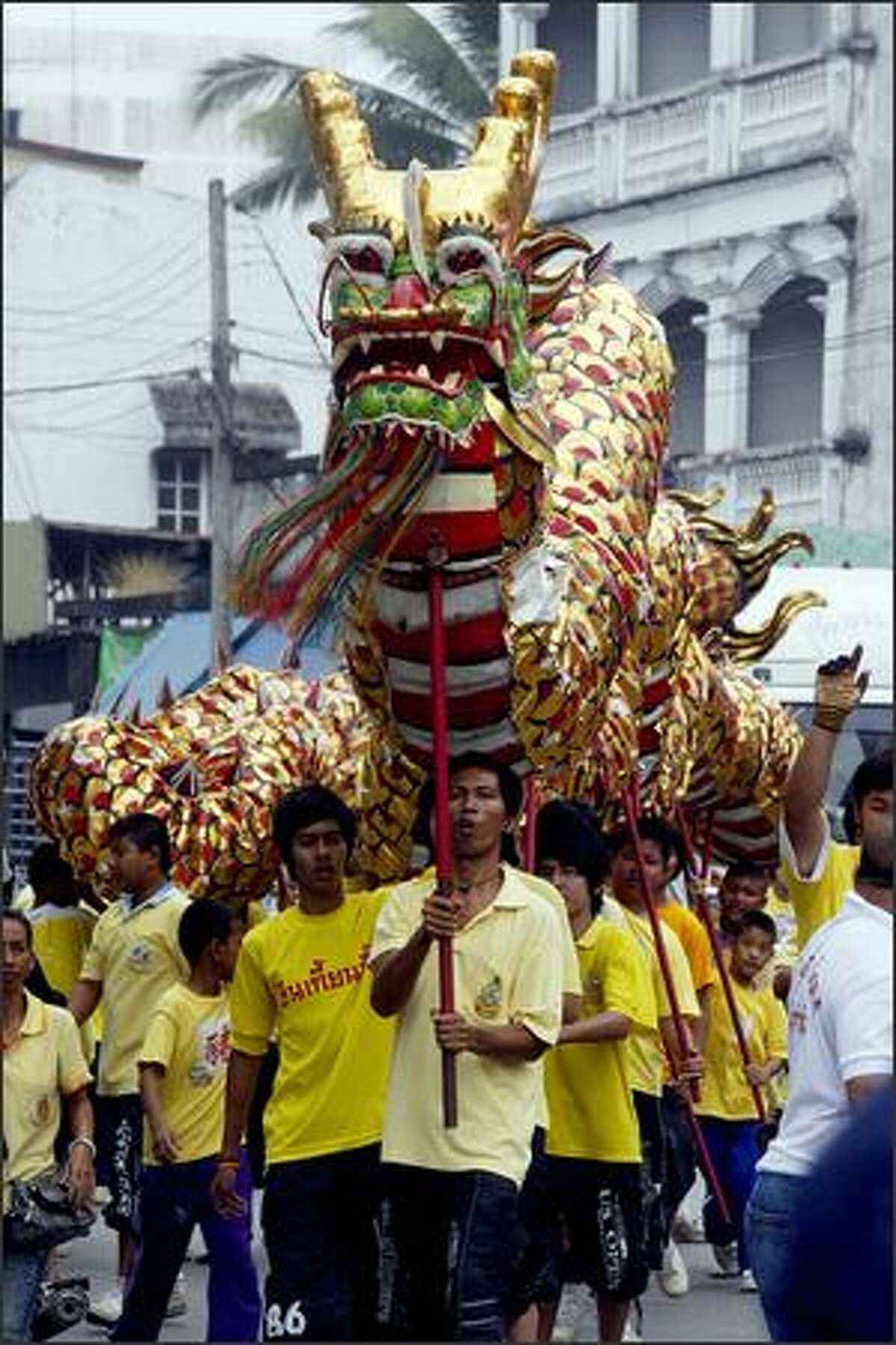Thai entertainers parade a dragon outside a Chinese temple in Pattani, southern Thailand, on the eve of the Chinese New Year.