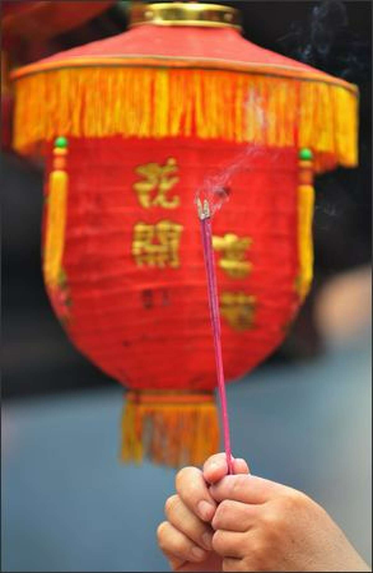 A worshipper holds incense sticks in front of a lantern during Chinese Lunar New Year prayers in Jakarta.