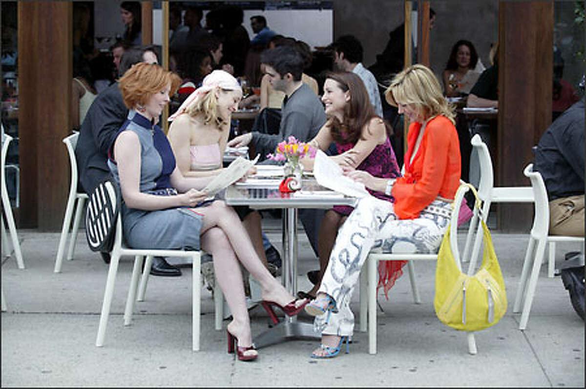 Miranda (Cynthia Nixon), Carrie (Sarah Jessica Parker), Charlotte (Kristin Davis) and Samantha (Kim Cattrall) step out for a bite.