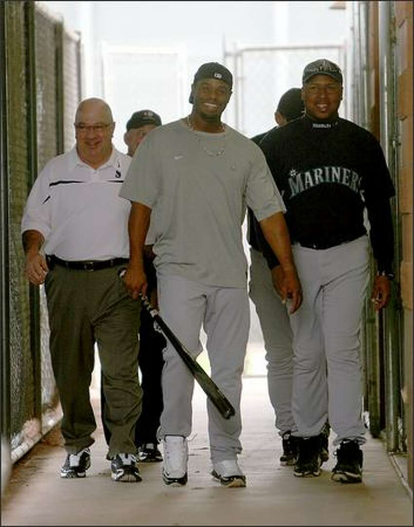 After taking 11 minutes of batting practice, Ken Griffey Jr. leaves the batting cage with Mariners general manager Jack Zduriencik (left).
