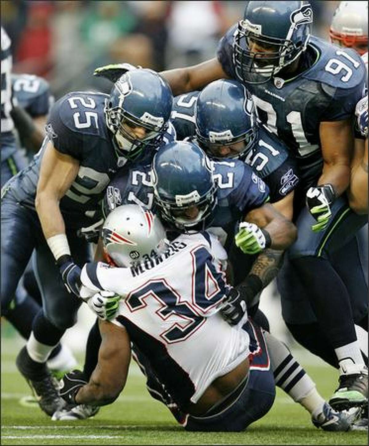 Seahawks safety Jordan Babineaux leads a group of defenders including (from left) Brian Russell, Lofa Tatupu and Baraka Atkins, as they bring down New England Patriots running back Sammy Morris after a short gain at Qwest Field in Seattle on Dec. 7.