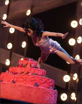 Singer Katy Perry leaps onto the cake. Photo: Getty Images