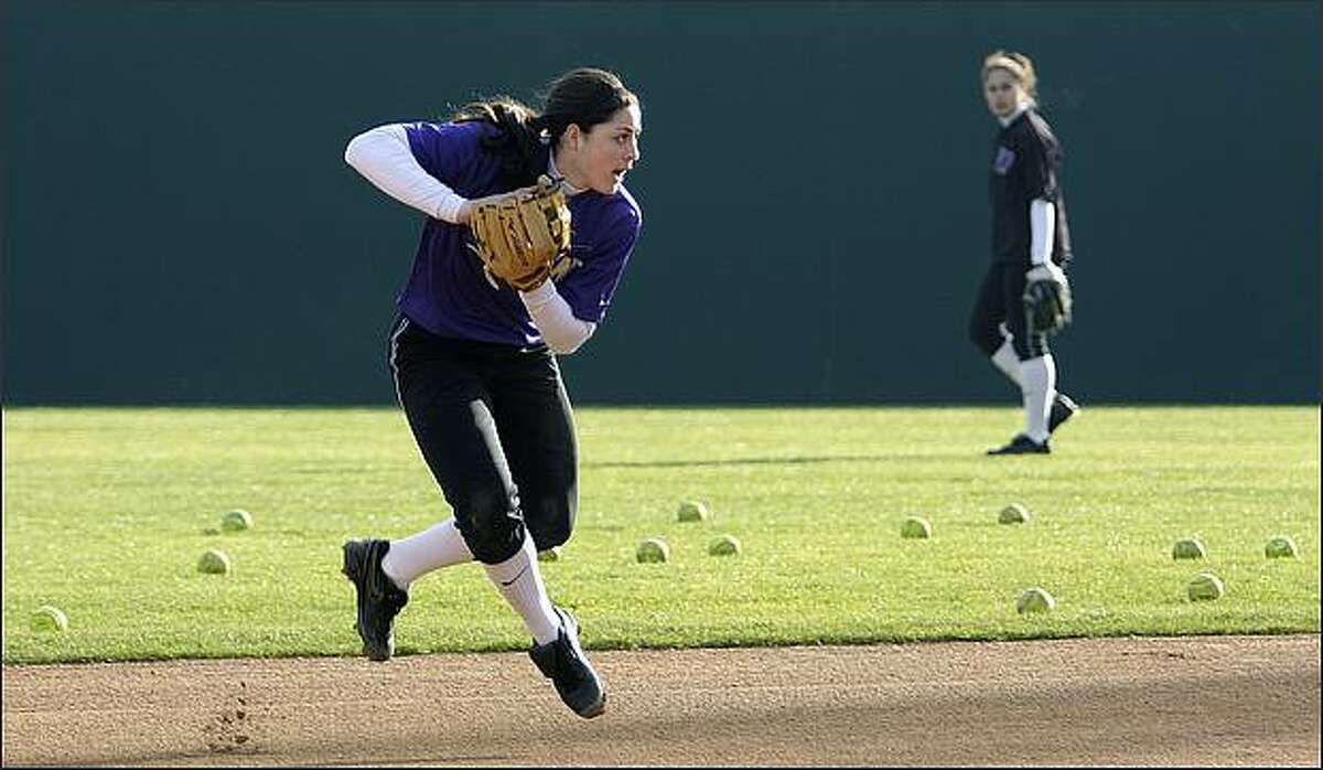Morgan Stuart fields a ball at shortstop as Ashley Tuiasosopo looks on from the outfield during University of Washington softball team practice at Husky Softball Stadium.