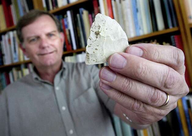 Texas A&M archaeology professor Michael Waters displays an artifact used by prehistoric man as a scraping and cutting tool in his office at Texas A&M University in College Station. Photo: Associated Press/Stuart Villanueva,  Bryan-College Station Eagle