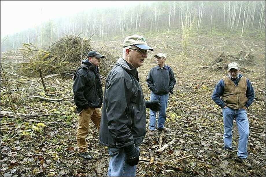Jimmy Collins, center, council president of the Pacific Harbors Council, with camp ranger Dan Collett, left, Doug Dorr, properties committee chairman, center back, and Joe Staley, forestry consultant, tour a timber harvest at Camp Delezene. Collins and Dorr have ties to Weyerhaeuser. Photo: Gilbert W. Arias/Seattle Post-Intelligencer