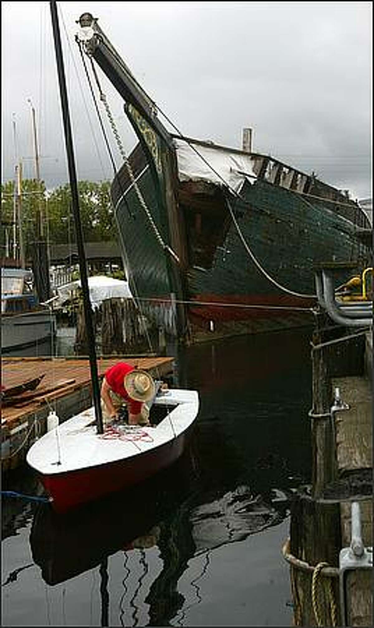 With the historic schooner Wawona moored behind him, Sterling Hines-Elzinga, 14, an intern at the Center for Wooden Boats, cleans his sailboat at South Lake Union Monday, Aug. 20, 2007.