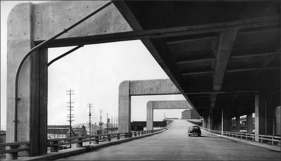 """Looking north along the nearly finished viaduct on March 4, 1954, near Lenora Street, where the lower deck carrying southbound traffic, edges under the top northbound deck. The original caption adds: """"Note the beauty that the giant concrete supports add to the viaduct."""" (Seattle P-I photo) Photo: Museum Of History And Industry"""