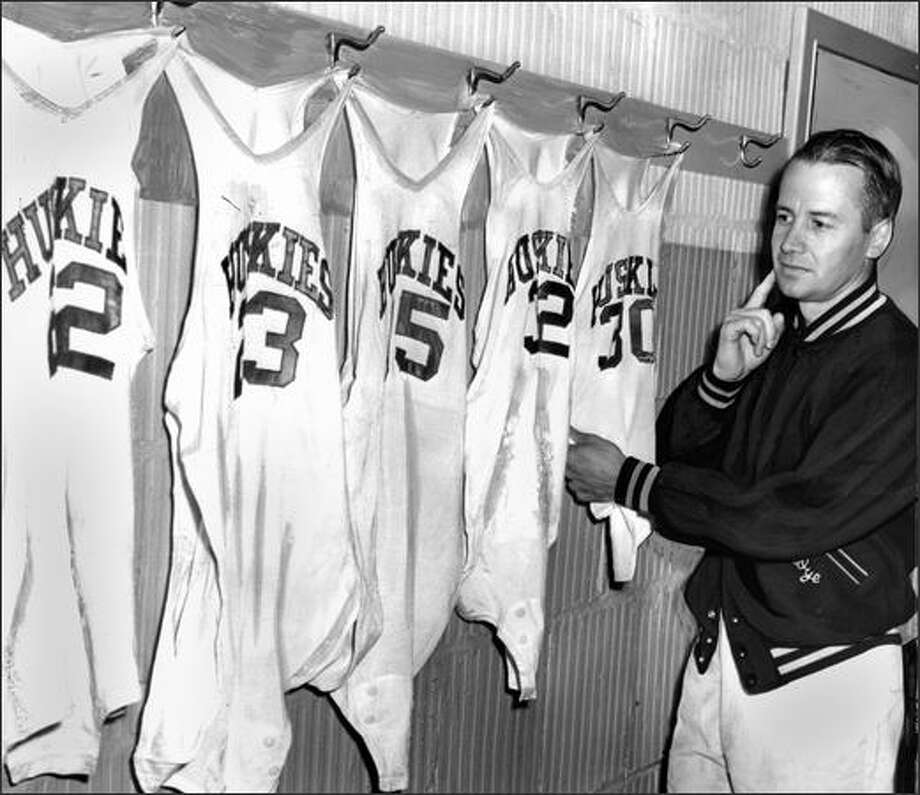 In 1953, Tippy Dye looks over the jerseys worn by his championship UW basketball team of the last three years. The jerseys, left to right, were worn by Mike McCutchen, Doug McClary, Bob Houbregs, Chuck Koon and Joe Cipriano. The players who filled these uniforms are gone and Dye must rebuild. (P-I photo by Ken Harris) Photo: Museum Of History And Industry