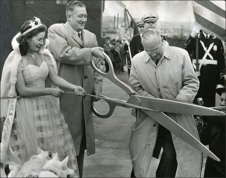 Cutting the ribbon to open the Alaskan Way Viaduct on April 4, 1953, are, from left, Iris Adams, Mayor Allan Pomeroy and D.K. MacDonald, president of the Automobile Club of Washington. (Seattle P-I photo) Photo: Museum Of History And Industry