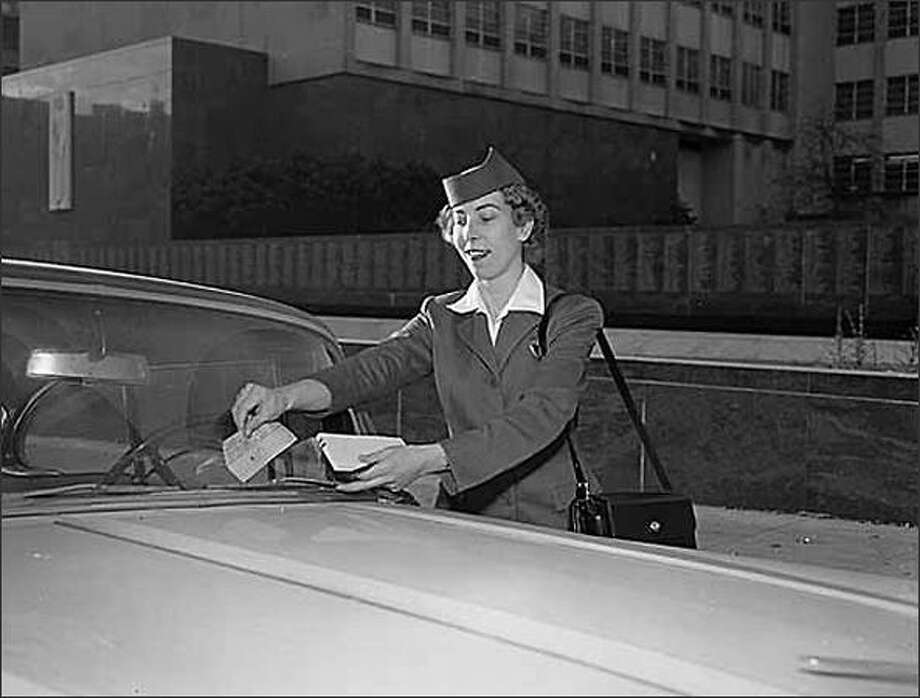 Meter maid Rose Marie Sillence ticketing a car, Seattle, November 26, 1957. (Seattle Post-Intelligencer Collection, Museum of History & Industry 1986.5.9850.2) Photo: Museum Of History And Industry