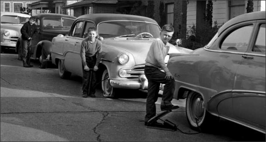 "From Life Magazine, February 17, 1958: ""A punishment fitting the crime found three young boys in Seattle busy pumping up automobile tires. A patrolman and the father of one of the boys made them do it after they let the air out of tires on 40 cars and trucks. When the boys pumped 16 tires, the father rented a power pump."" (P-I photo by Phil H. Webber) Photo: Museum Of History And Industry"