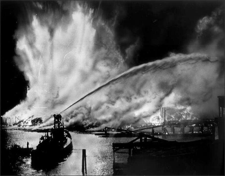 "This view from the Ballard Bridge shows flame and smoke streaming from the Seattle Cedar Lumber Manufacturing Co. plant on the night of May 20, 1958. Fireboat pours water onto the fire, which leaps hundreds of feet into the air from the kiln and storage areas. Damage from the blaze was estimated at $1.5 million. Heat from the king-size blaze was felt more than two city blocks away."" (P-I photo by Phil H. Webber) Photo: Museum Of History And Industry"