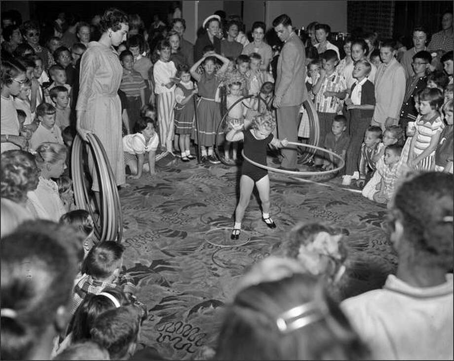 The national hula hoop craze was in full force in October 1958 when more than 700 area boys and girls w-hooped it up in a competition at the Frederick & Nelson Tea Room. More than 100 million of the colorful rings sold that year for $1.98 each. (P-I photo by Phil H. Webber) Photo: Museum Of History And Industry