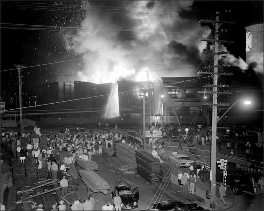 Firefighters fought a three-alarm blaze at the Seattle Cedar Lumber Manufacturing Co. in Ballard on May 21, 1958. Flames rose hundreds of feet in the air, and the heat could be felt two blocks away. The fire, which spread quickly throught the stacks of lumber, caused more than $1.5 million in damage. (P-I photo by Phil H. Webber) Photo: Museum Of History And Industry