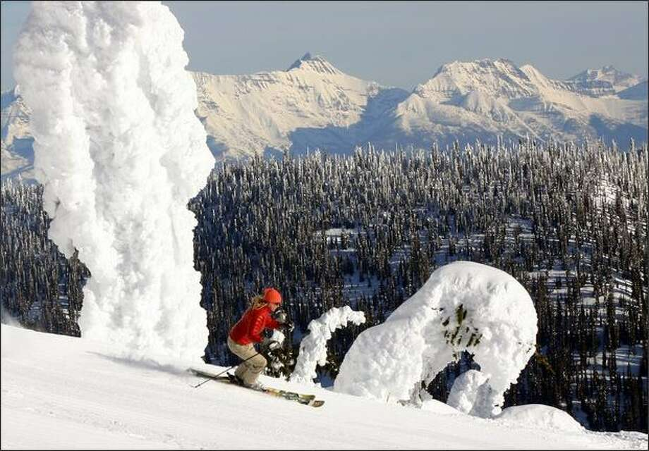 A skier near the summit of Big Mountain at Whitefish Mountain Resort glides by the signature snow ghosts with the peaks of Glacier National Park in the background. Photo: Brian Schott