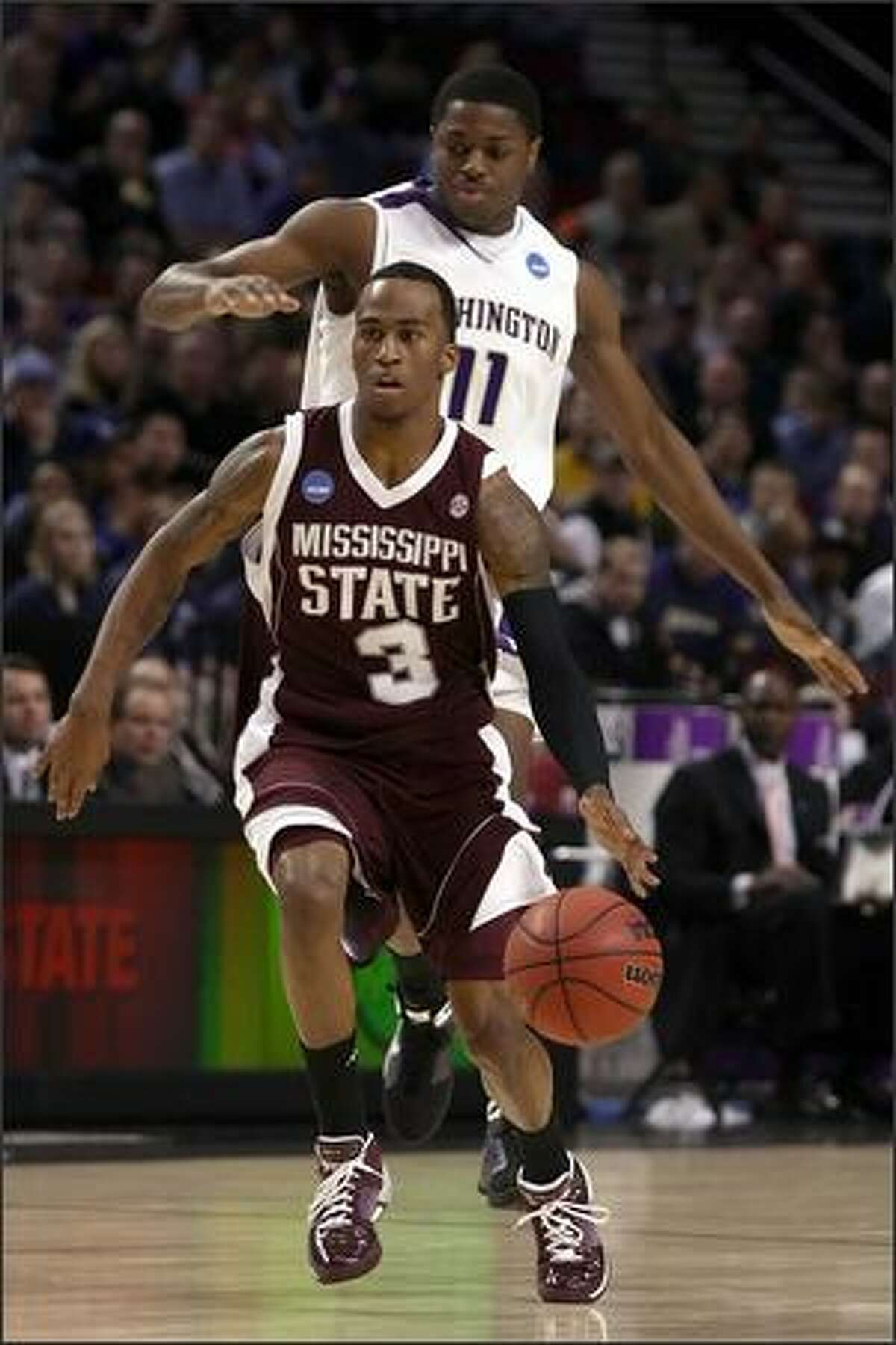 Dee Bost of Mississippi State moves the ball in front of Matthew Bryan-Amaning of Washington in the first half.