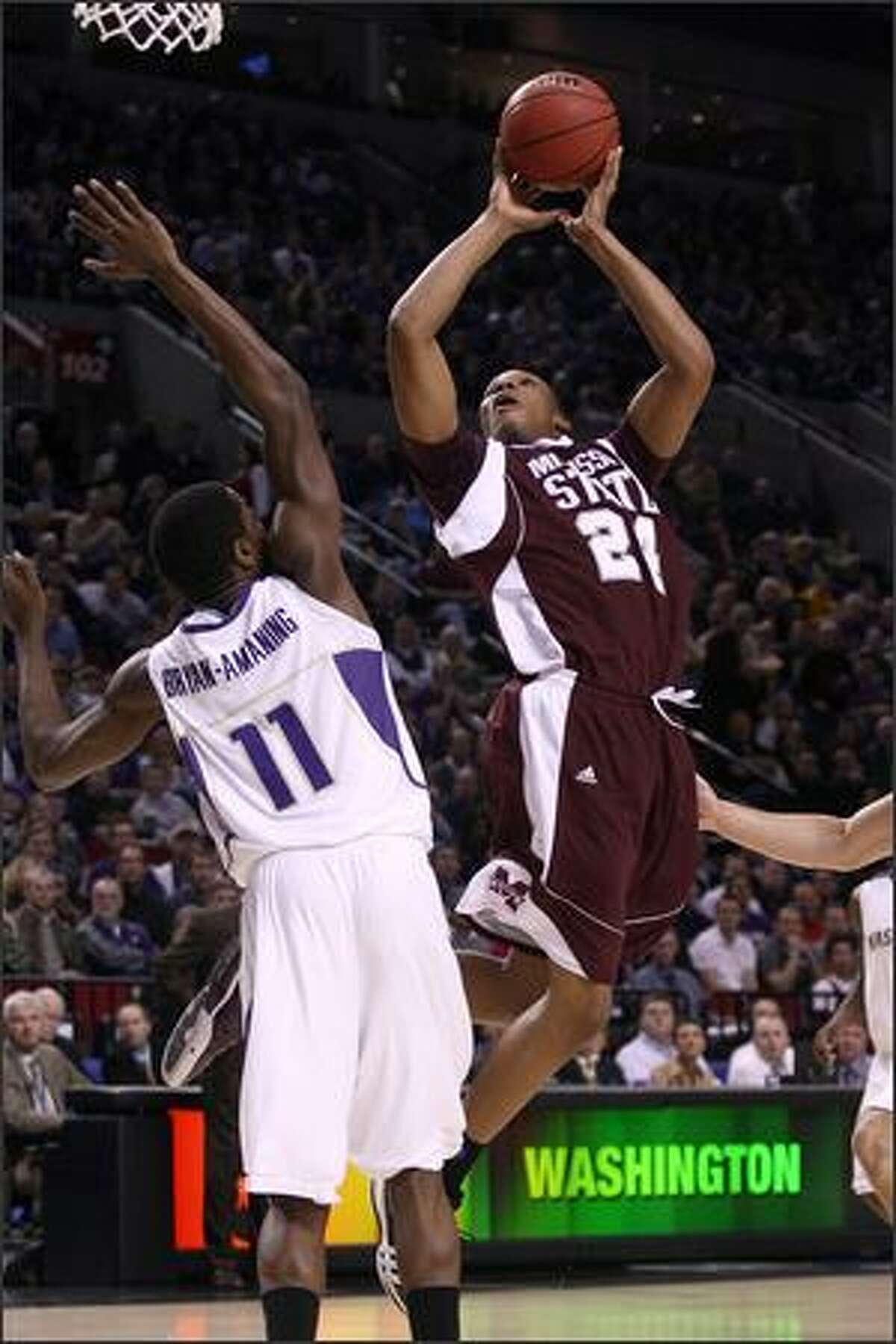Kodi Augustus of Mississippi State goes up for a shot over Matthew Bryan-Amaning of Washington in the first half.
