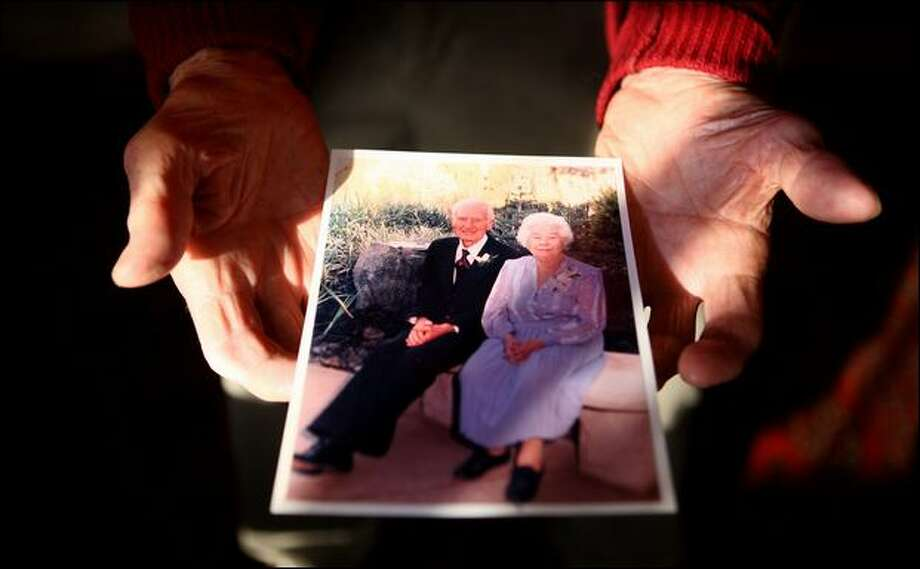 Don Nettleblad holds a photo of him and Kathryn, his wife of 71 years. At 93, he is now the sole caregiver for Kathryn, 94, who has Alzheimer's. Photo: Joshua Trujillo/Seattle Post-Intelligencer