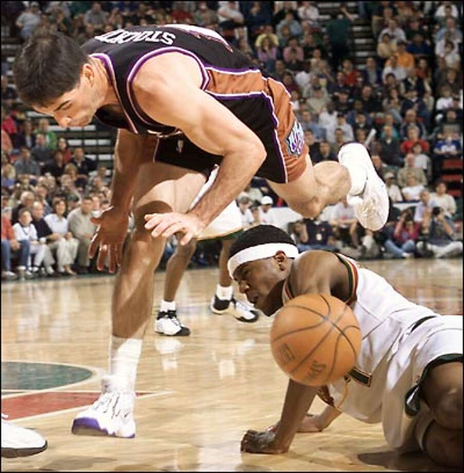 The Utah Jazz's John Stockton trips over Sonic Shammond Williams during a struggle for a loose ball in the second half of Game 3 of the first round of the NBA Playoffs in KeyArena. Photo: Dan DeLong, Seattle Post-Intelligencer