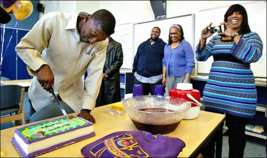 "Desmond Trufant cuts a cake that reads ""Bow down to Washington,"" as his mother, Constance, takes photos. The Wilson High product from Tacoma signed with the UW. Photo: Drew Perine/Associated Press"