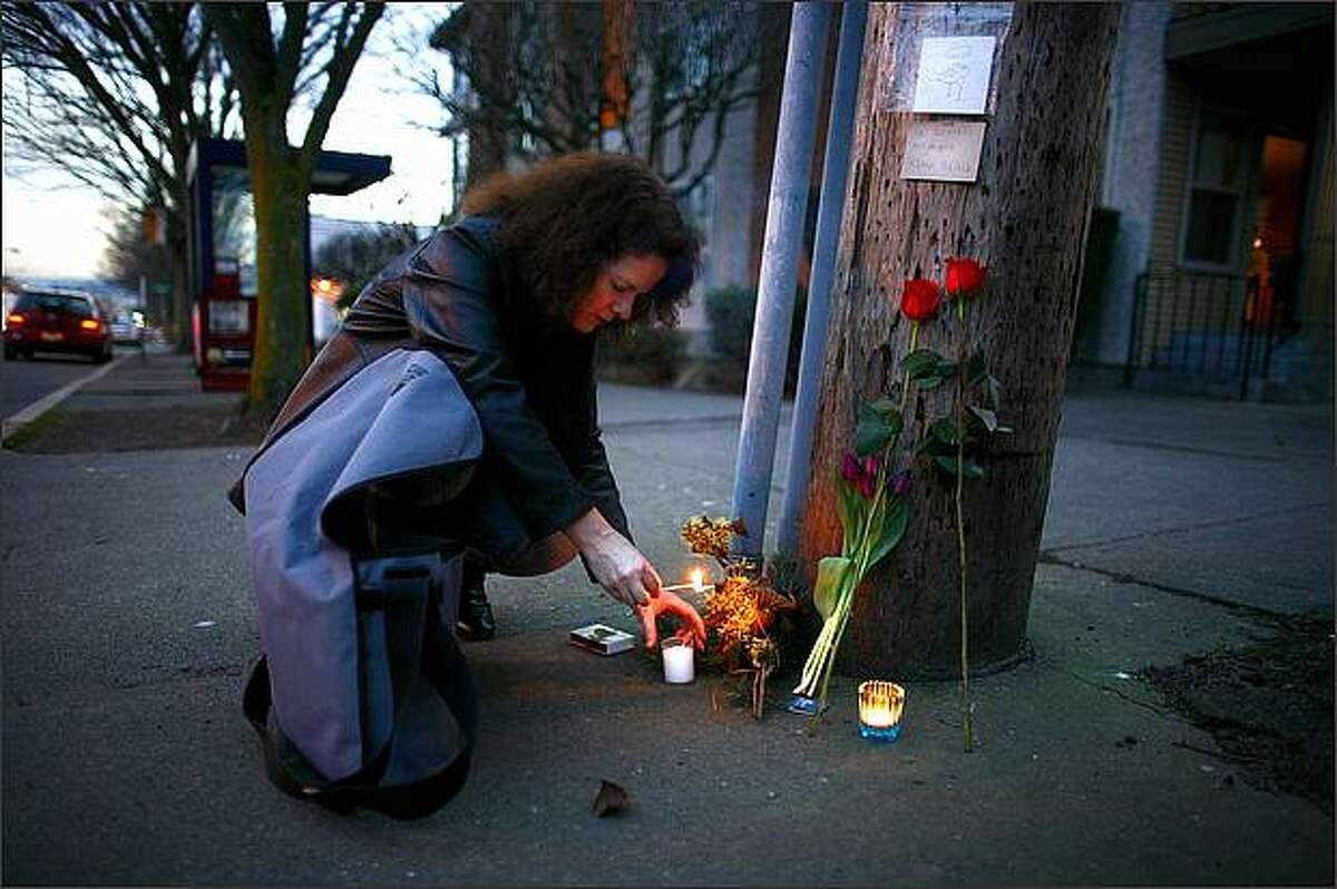 Elizabeth Schirmer lights a candle at a memorial for bicyclist Kevin Black, a 39-year-old father of two who died after colliding with a van Wednesday on 24th Avenue Northwest in Ballard. Schirmer's brother-in-law was involved in a serious motorcycle accident in 2007 at the same intersection. Investigators are still trying to piece together what happened Wednesday.