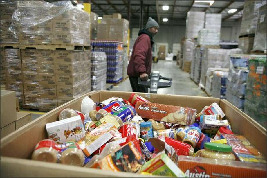 Anthony Brown, volunteer coordinator at Northwest Harvest's Kent warehouse, moves a container with a variety of products containing peanuts into storage Thursday. Photo: Paul Joseph Brown/Seattle Post-Intelligencer
