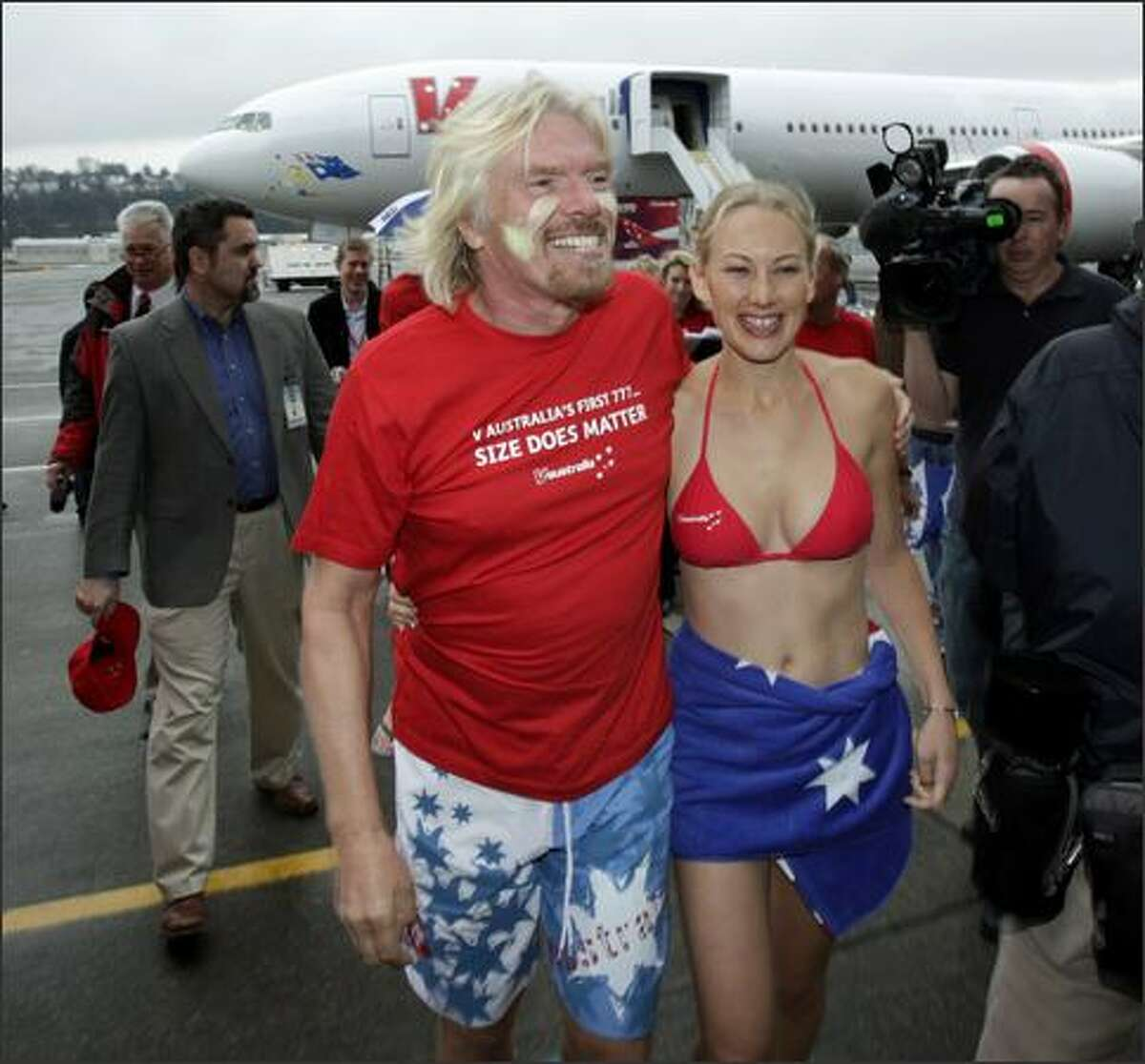 Sir Richard Branson, chairman of Virgin Group, walks with cabin crewmember Catherine Blackbee as they attend a delivery ceremony Friday for a Boeing Co. 777-300ER airplane in Seattle. The plane will serve the Los Angeles-to-Sydney route for Virgin's new V Australia airline.