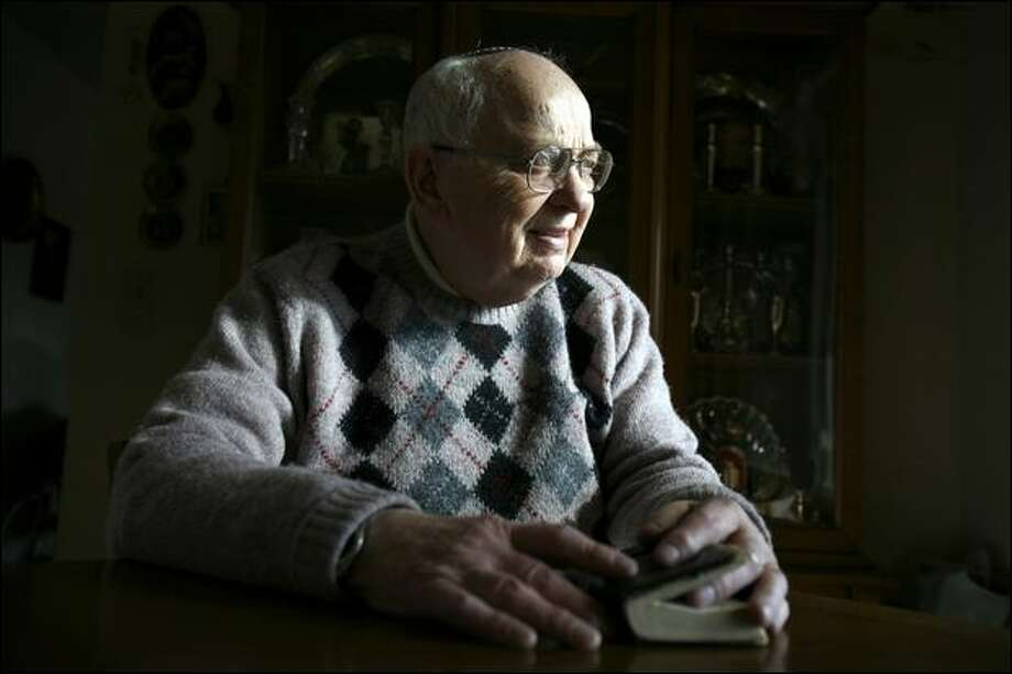 Rainier Valley resident Abraham Traub is among dozens of Holocaust survivors in the Seattle area applying for compensation from Germany for the victims of Nazis. Traub holds his sidur, a Jewish book of daily prayers. Photo: Paul Joseph Brown/Seattle Post-intelligencer Photos