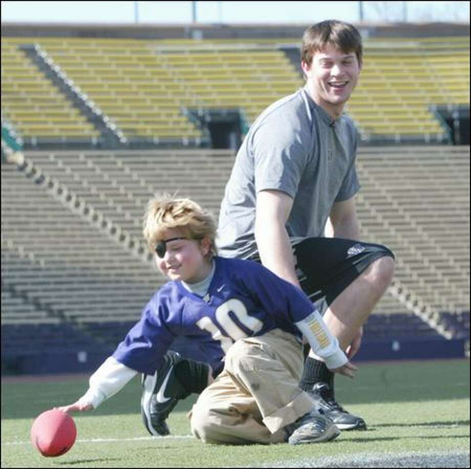 Kyle Roger goes after the ball after a punt as Huskies quarterback Jake Locker watches in a day of play at Husky Stadium in 2007. Roger died of brain cancer at the age of 8 on Saturday. Photo: Grant M. Haller/Seattle Post-Intelligencer