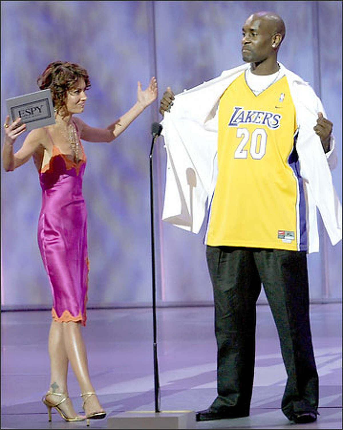 Actress Lara Flynn Boyle reacts as new Los Angeles Laker Gary Payton unveils a Lakers jersey before they present an award together during the 11th annual ESPY Awards, Wednesday, July 16, 2003, in Los Angeles. The ESPY Awards honor the year's top performances and sports moments. (AP Photo/Kevork Djansezian)