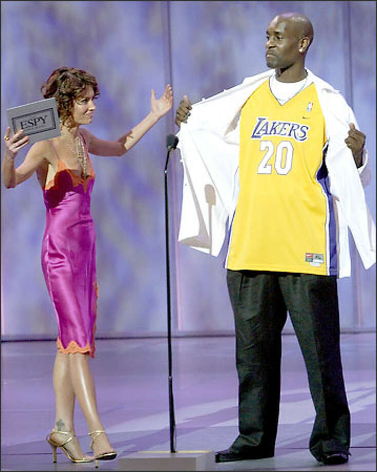 Actress Lara Flynn Boyle reacts as new Los Angeles Laker Gary Payton unveils a Lakers jersey before they present an award together during the 11th annual ESPY Awards, Wednesday, July 16, 2003, in Los Angeles. The ESPY Awards honor the year's top performances and sports moments. (AP Photo/Kevork Djansezian) Photo: Associated Press