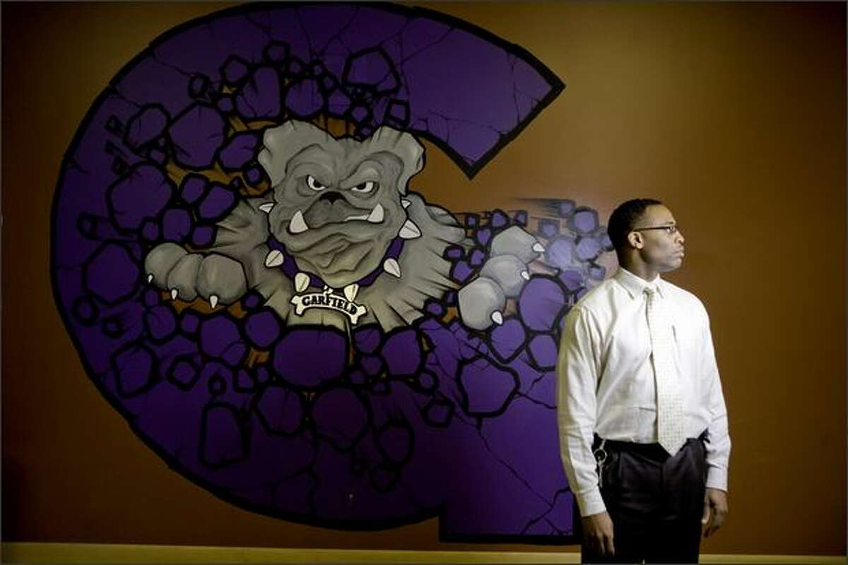 Garfield High School Principal Ted Howard, next to the school's Bulldogs logo, is urging more communication between urban and suburban students.