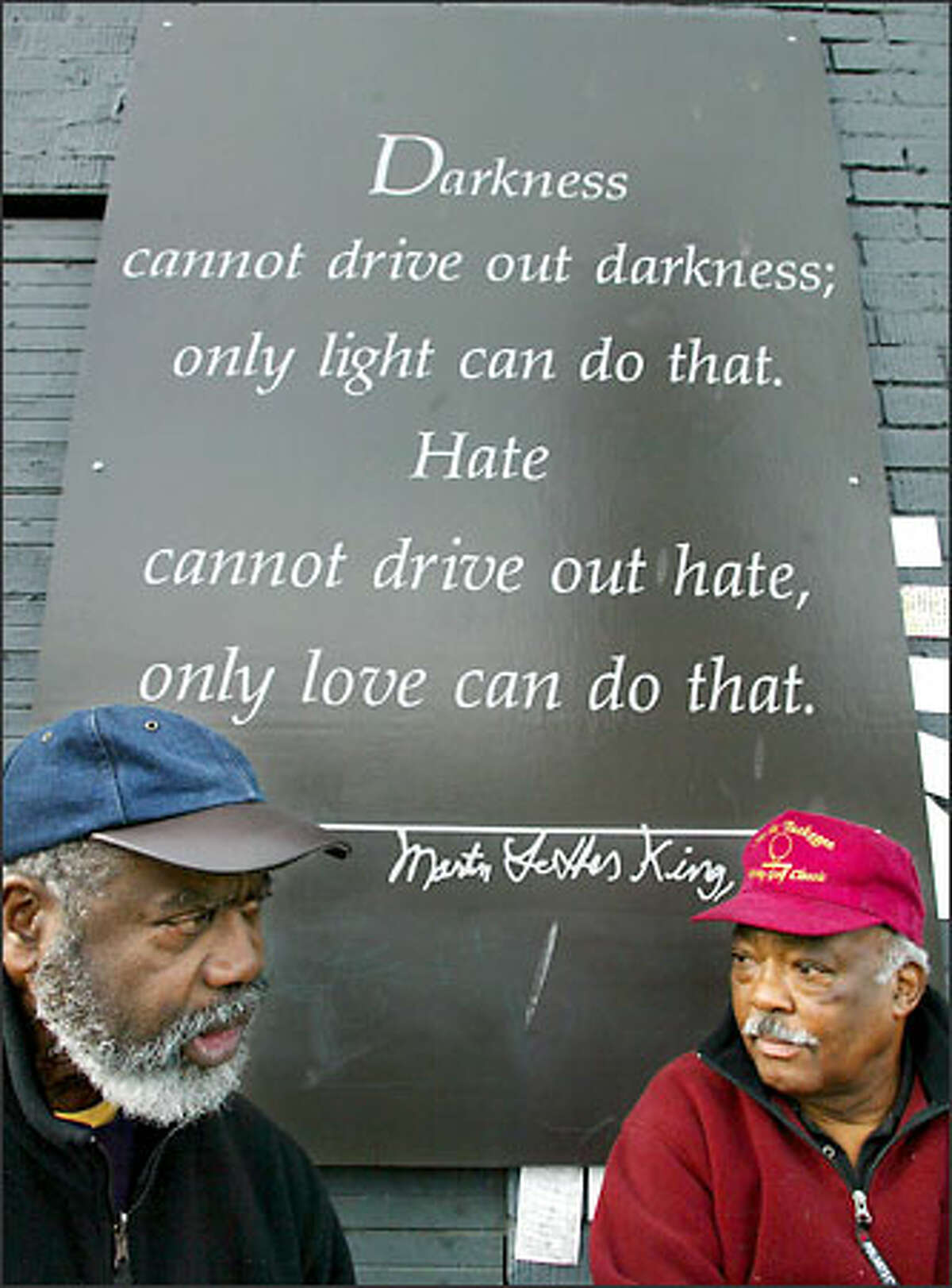 Fifty-year-long friends Frank Jones, left, and Dell Durden pause to reflect on the impact of Martin Luther King Jr. after lunching at Catfish Corner in the Central District. A mural and this quotation from King cover the east-facing wall of the restaurant.