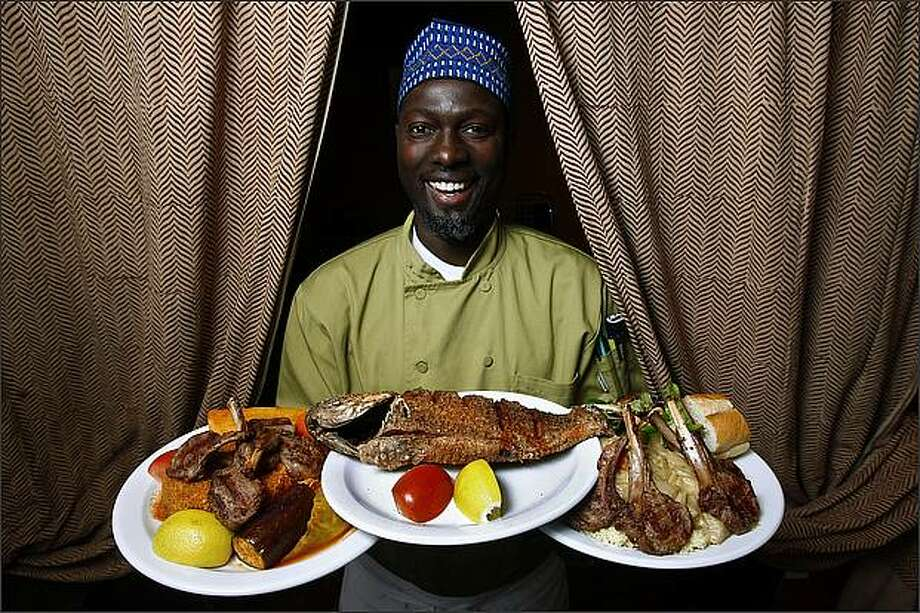 Jacques Sarr shows off his debe, grilled tilapia and yassa au poulet. Photo: Andy Rogers/Seattle Post-Intelligencer