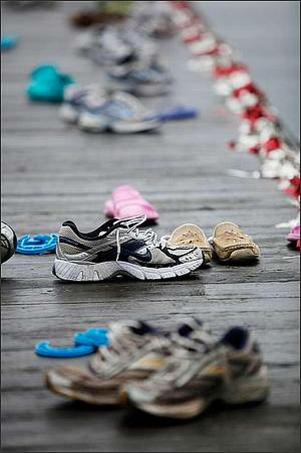 Shoes line the Shellhouse dock while the team practices on Lake Washington. Photo: Clifford DesPeaux, Special To The Seattle Post-Intelligencer