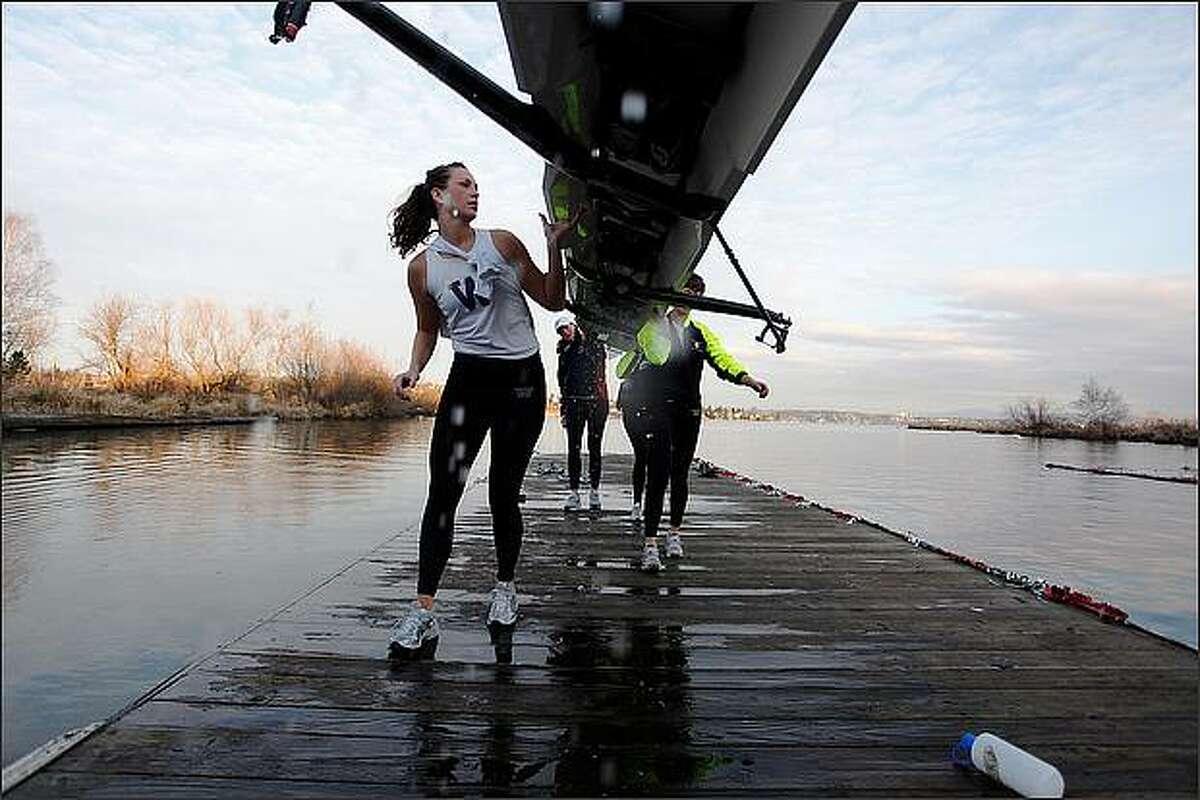 University of Washington sophomore Kira O'Sullivan, left, helps carry a boat back to the Conibear Shellhouse after a practice on Lake Washington.