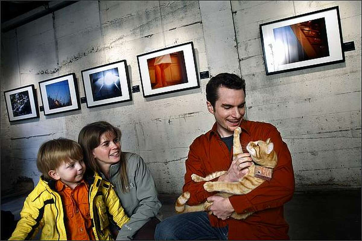 Michael Cross cuddles with Cooper the cat so that Doree Armstrong and her son Alex, 3, can get a closer look at the artist during a pre-opening show for the press at Urban Light Studios in the Greenwood Collective.