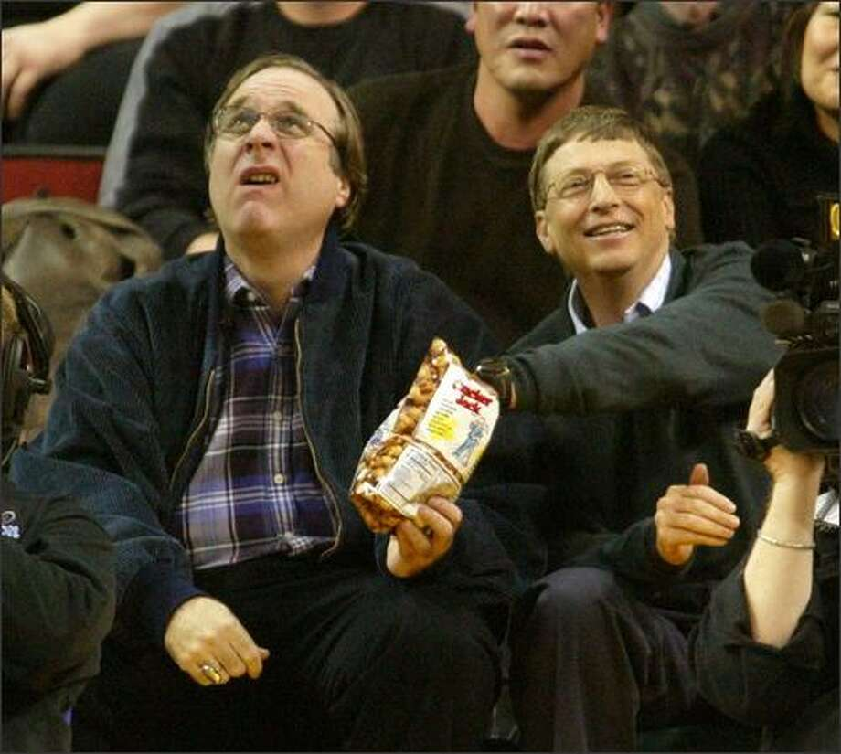 Paul Allen keeps a wary eye on the scoreboard as Bill Gates helps himself to Allen's Cracker Jacks during a Seattle Sonics game against Allen's Portland Trail Blazers at KeyArena on Jan. 5, 2004. Photo: P-I File