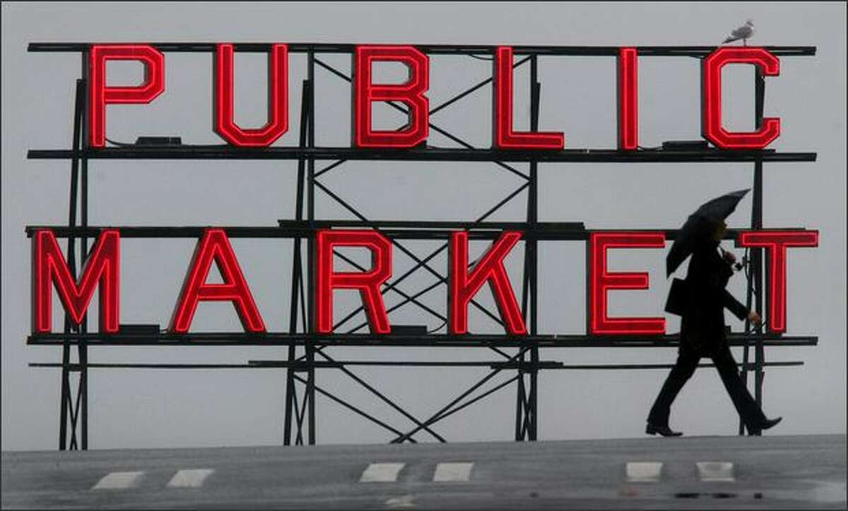 An umbrella-toting pedestrian crosses Pine Street along First Avenue in downtown Seattle during a dreary winter day in front of one of the Pike Place Market's signature neon signs. (Joshua Trujillo, Seattle P-I)