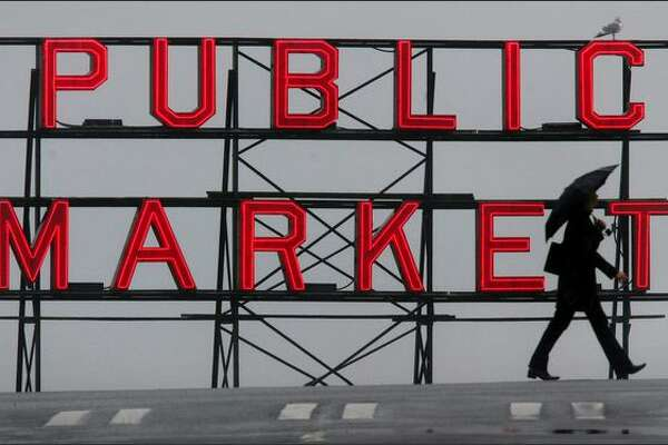 An umbrella-toting pedestrian crosses Pine Street along First Avenue in downtown Seattle on Wednesday Jan. 14, 2004, during a dreary winter day in front of one of the Pike Place Market's signature neon signs. (Joshua Trujillo, Seattle P-I)