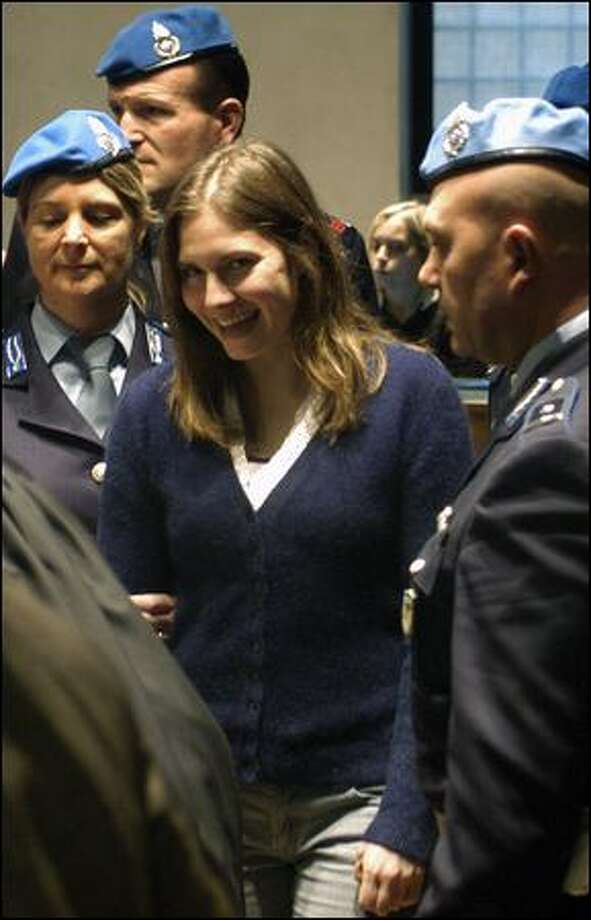 Amanda Knox flashes a smile as she is escorted inside the Perugia, Italy, courtroom Friday to stand trial for murder. Photo: Stefano Medici/Associated Press